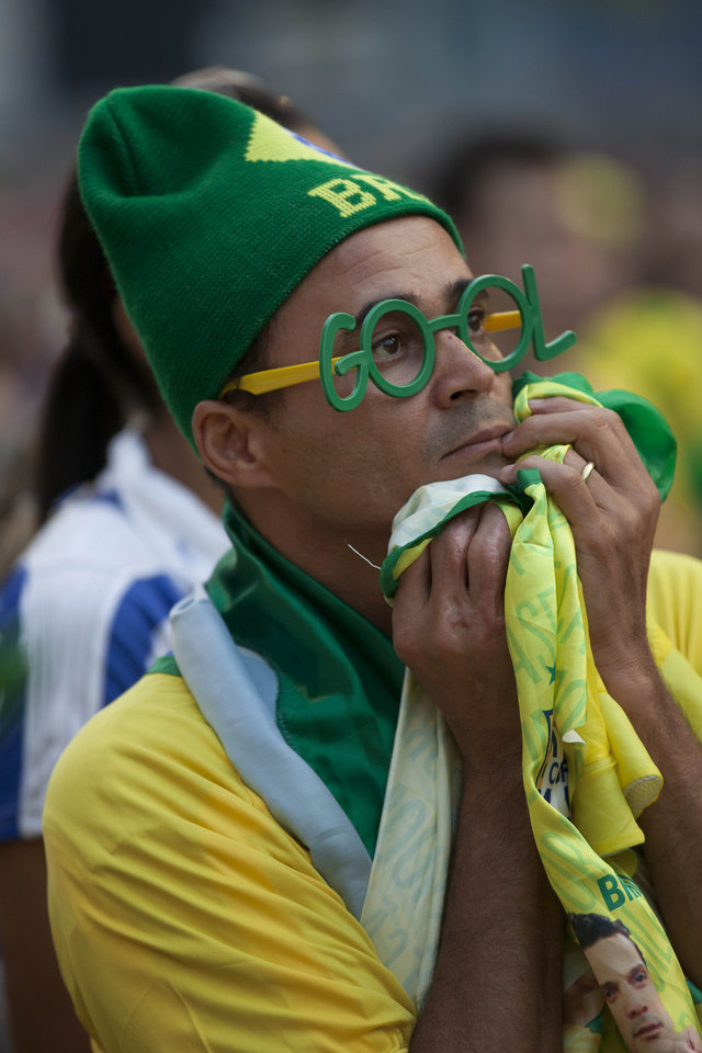 Photo - A fan wearing Brazilian national soccer team colors watches the World Cup group A soccer match between Mexico and Brazil on a giant screen at the FIFA Fan Fest in Sao Paulo, Brazil, Tuesday, June 17, 2014. Mexico went on to hold host Brazil to a 0-0 draw. (AP Photo/Dario Lopez-Mills)