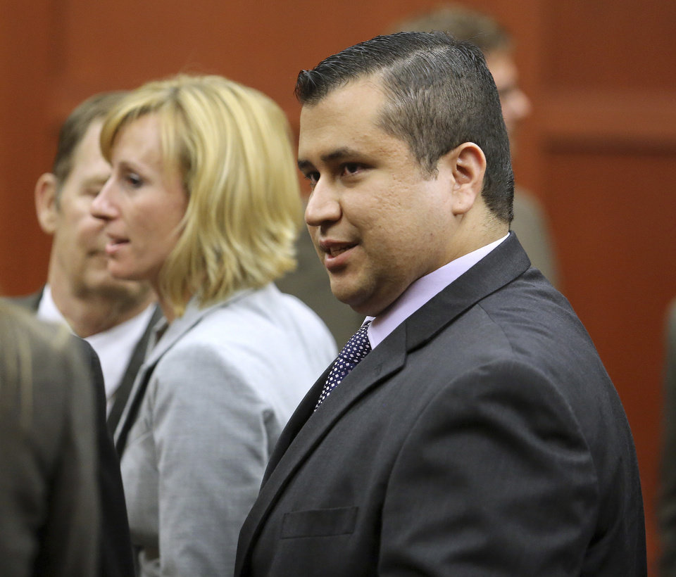 Photo - George Zimmerman leaves court with his family after Zimmerman's not guilty verdict was read in Seminole Circuit Court in Sanford, Fla. on Saturday, July 13, 2013. Jurors found Zimmerman not guilty of second-degree murder in the fatal shooting of 17-year-old Trayvon Martin in Sanford, Fla. (AP Photo/Joe Burbank, Pool) ORG XMIT: FLJR412