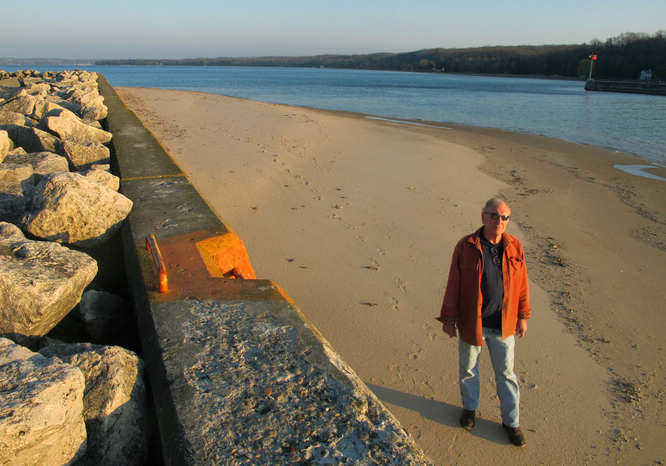 In this Nov. 16, 2012 photo, Jim Simons, who runs a rod and reel repair business in Onekama, Mich., strolls on a sand bar alongside the Portage Lake channel that leads to Lake Michigan at Onekama, Mich. The sand bar normally would be submerged in water, but low Great Lakes levels have exposed the shoreline in many areas, causing problems for boaters and tourist businesses in small harbor towns. The Great Lakes, the world�s biggest freshwater system, are dropping because of drought and climbing temperatures, a trend that accelerated with this year�s almost snowless winter and scorching summer. (AP Photo/John Flesher)