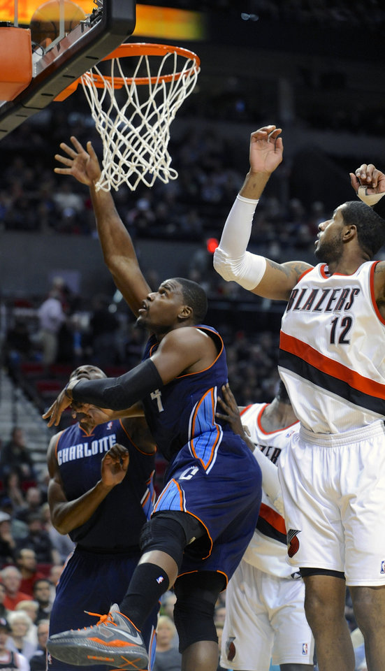 Photo - Charlotte Bobcats' Jeff Adrien (4) shoots against Portland Trail Blazers' LaMarcus Aldridge (12) during the first half of an NBA basketball game in Portland, Ore., Monday, March 4, 2013. (AP Photo/Greg Wahl-Stephens)