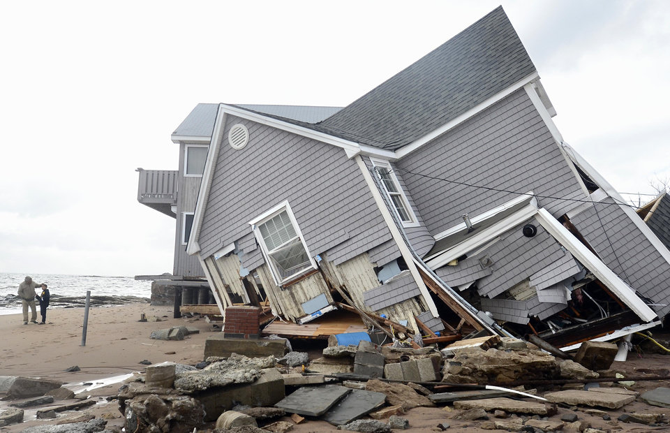 People stand next to a house collapsed from superstorm Sandy in East Haven, Conn. on Tuesday, Oct. 30, 2012. (AP Photo/Jessica Hill) ORG XMIT: CTJH107