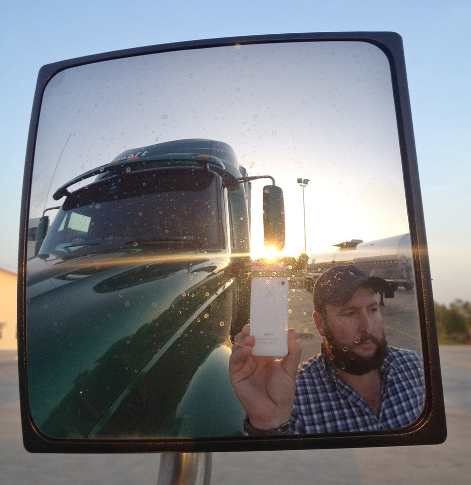 This undated image provided by James Weitze shows a truck driver taking a self portrait on the road. Weitze satisfies his video fix with an iPhone. He sleeps most of the time in his truck, and has no apartment. To be sure, he's an extreme case and probably wouldn't fit into Nielsen's definition of a household in the first place. But he's watching Netflix enough to keep up on shows like �Weeds,� �30 Rock,� �Arrested Development,� �Breaking Bad,� �It's Always Sunny in Philadelphia� and �Sons of Anarchy.� (AP Photo/James Weitze)