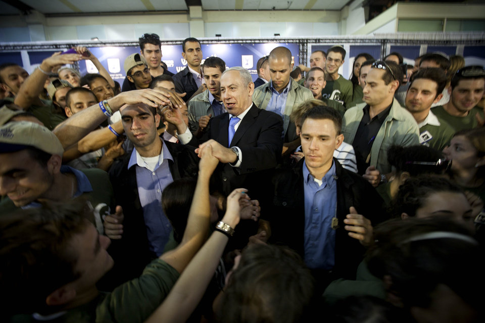 Israel's Prime Minister Benjamin Netanyahu, center, greets new Jewish immigrants from U.S. as they arrive at the Ben Gurion airport near Tel Aviv, Israel, Tuesday, Aug. 14, 2012. A total of 350 immigrants arrived on the flight from the U.S. Tuesday. Over 100 of the new immigrants are expected to join the Israel Defense Forces in the upcoming month.(AP Photo/Oded Balilty)