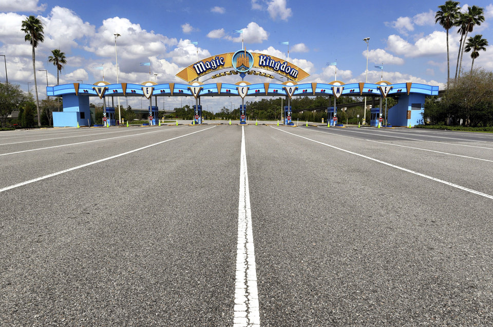Photo - FILE - In this March 24, 2020, file photo, lanes leading to the parking plaza entrance of Walt Disney World's Magic Kingdom sit empty during its second week of closure in response to the coronavirus pandemic in Orlando. From Cape Cod to California, festivals are being canceled, businesses in tourist havens are looking at empty reservation books, and people who have been cooped up through a dismal spring are worrying summer will bring just more of the same. (Joe Burbank/Orlando Sentinel via AP, File)
