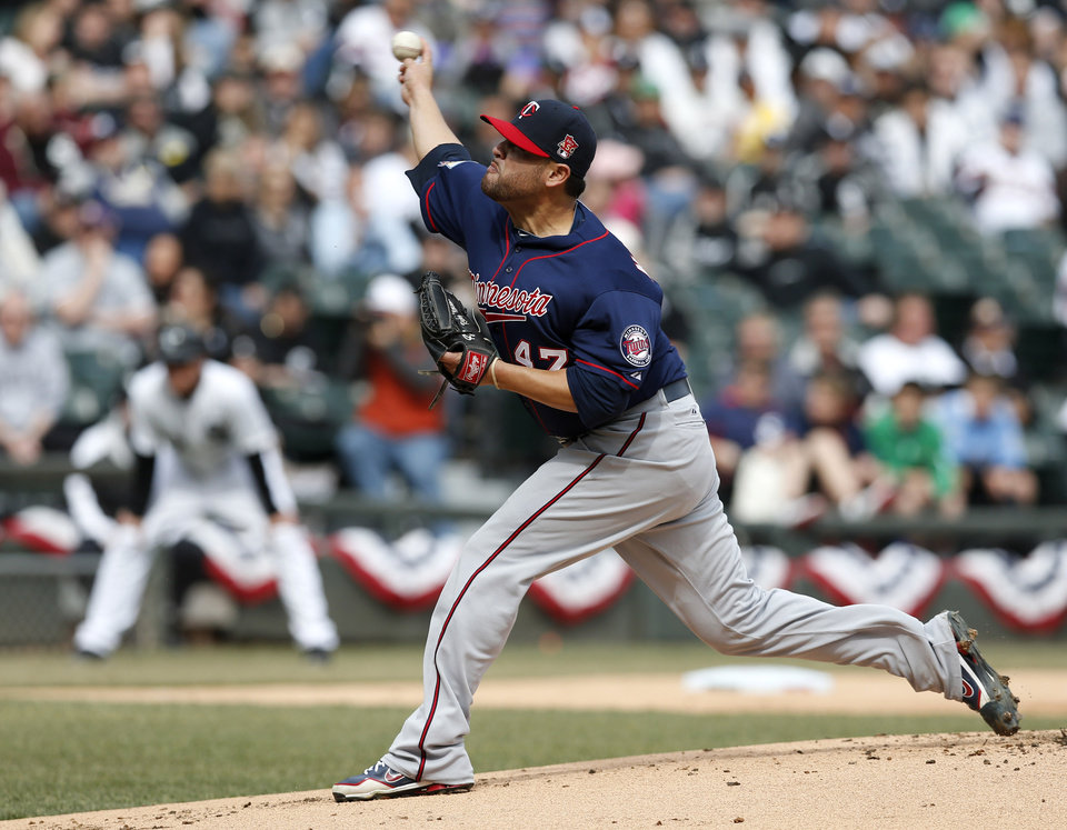Photo - Minnesota Twins starting pitcher Ricky Nolasco delivers during the first inning of an Opening Day baseball game against the Chicago White Sox Monday, March 31, 2014, in Chicago. (AP Photo/Charles Rex Arbogast)