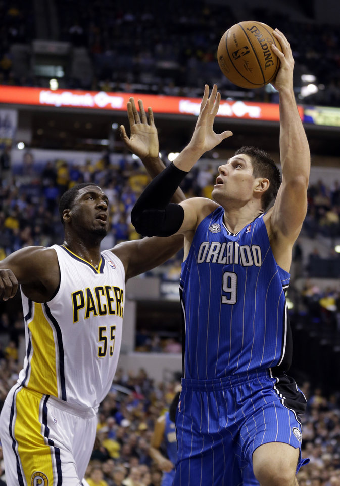 Photo - Orlando Magic center Nikola Vucevic, right, shoots over Roy Hibbert in the first half of an NBA basketball game in Indianapolis, Monday, Feb. 3, 2014.  (AP Photo/Michael Conroy)