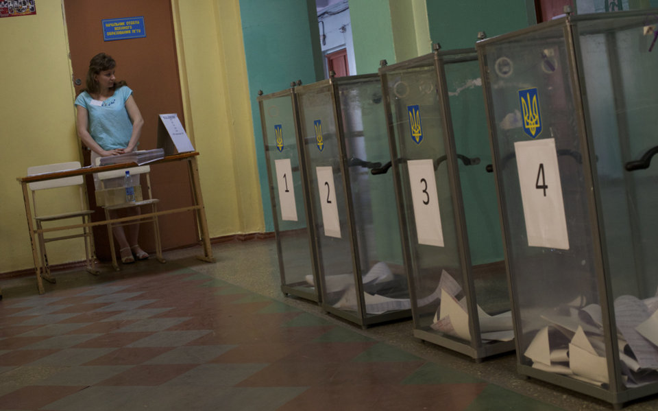 Photo - An election commission member waits for local residents at a polling station in Mariupol, Ukraine, on Sunday, May 25, 2014. Ukraine's critical presidential election got underway Sunday under the wary scrutiny of a world eager for stability in a country rocked by a deadly uprising in the east. (AP Photo/Ivan Sekretarev)