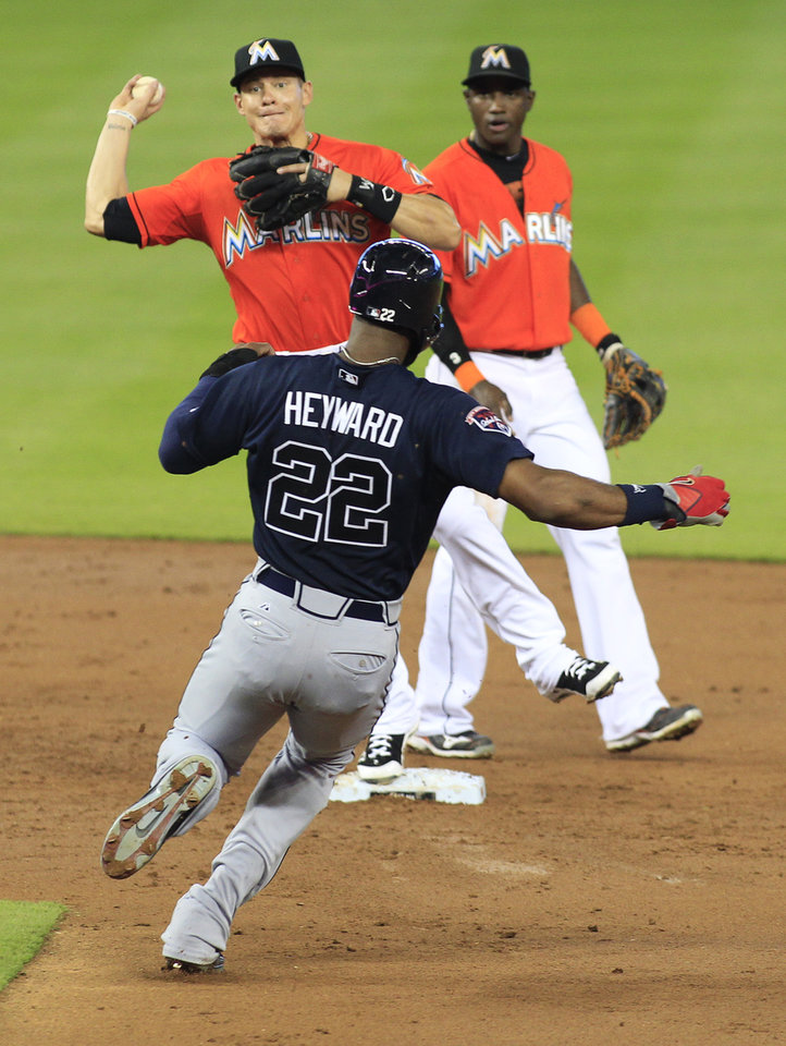 Photo - Atlanta Braves' Jason Heyward is forced out by Miami Marlins second baseman Derek Dietrich, left, as shortstop Adeiny Hechavarria looks on at right, on a fielder's choice which scored Atlanta Braves' Andrelton Simmons in the third inning during their baseball game in Miami, Sunday, June 1, 2014. (AP Photo/Joe Skipper)