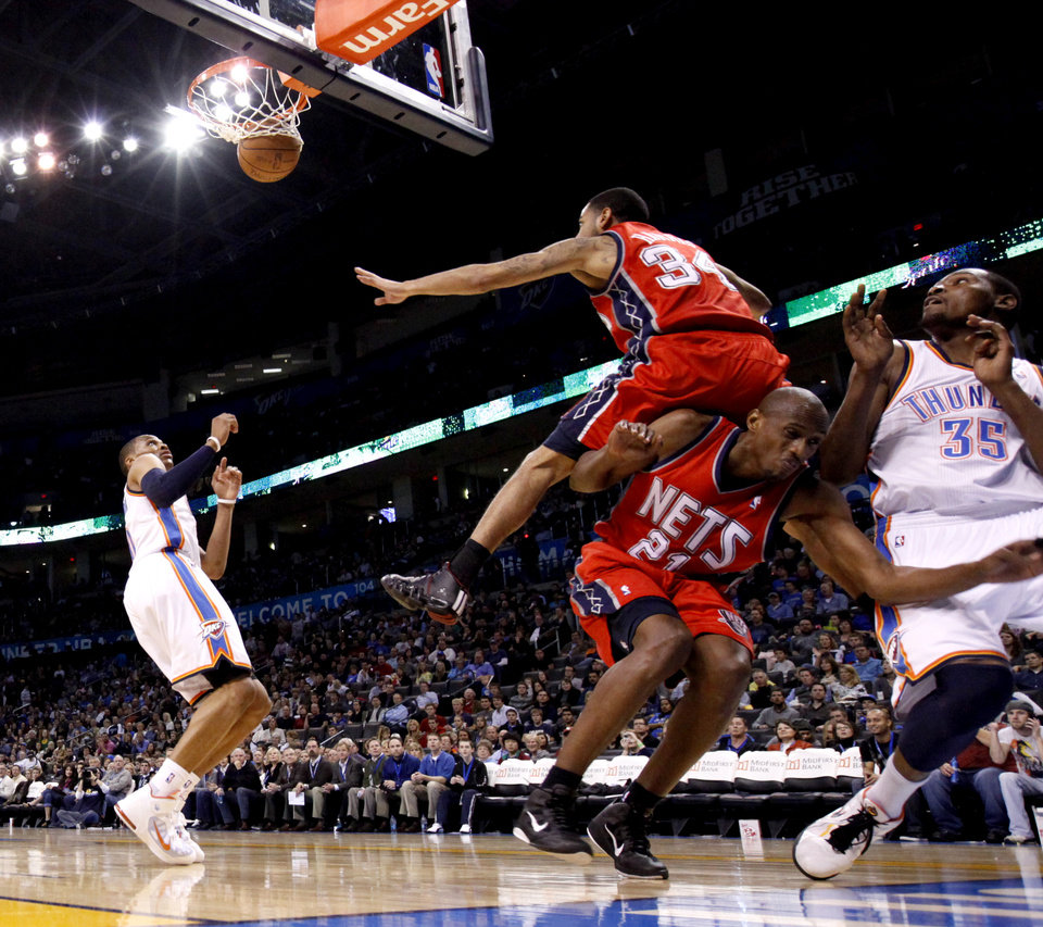Photo - Oklahoma City's Russell Westbrook, left, and Kevin Durant watch Durant's shot fall as New Jersey's Devin Harris, top, and Travis Outlaw collide during the NBA basketball game between the Oklahoma City Thunder and the New Jersey Nets at the Oklahoma City Arena, Wednesday, Dec. 29, 2010.  Photo by Bryan Terry, The Oklahoman