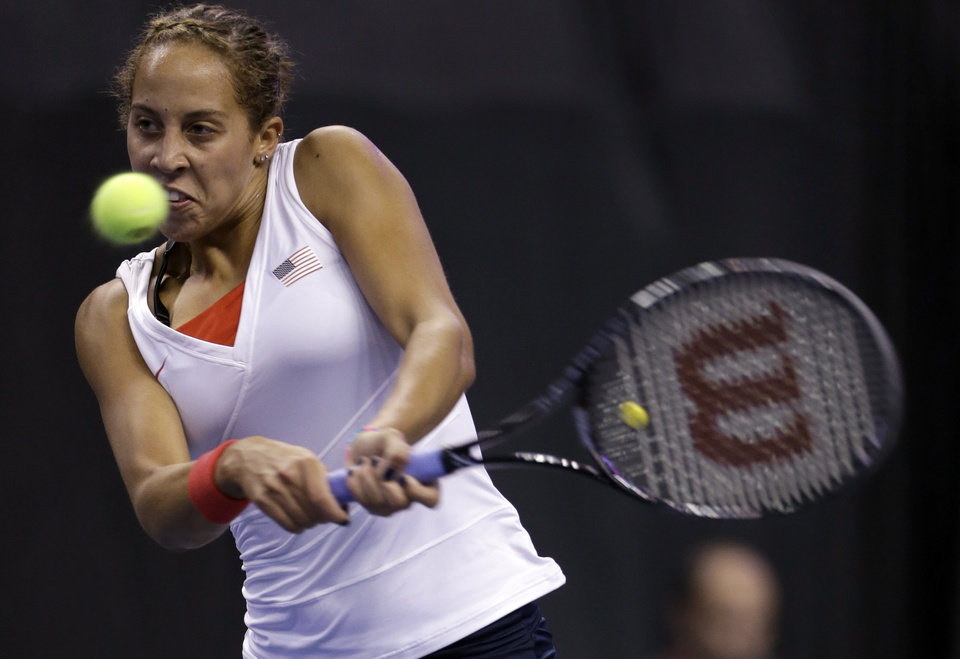 Photo - United States' Madison Keys returns a ball to France's Caroline Garcia during a Fed Cup singles world group playoff tennis match Sunday, April 20, 2014, in St. Louis. Garcia won 6-4, 6-3.(AP Photo/Jeff Roberson)