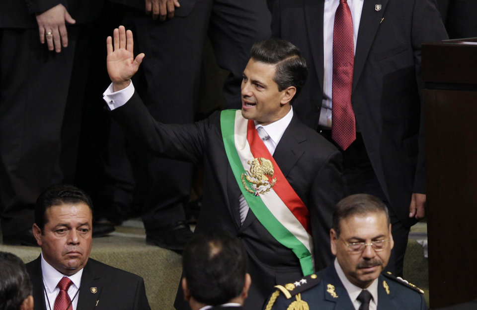 Photo - Mexico's incoming President Enrique Pena Nieto waves as he leaves his inauguration ceremony in congressional chambers, in Mexico City, Saturday, Dec. 1, 2012.  Pena Nieto took the oath of office as Mexico's new president on Saturday, bringing the old ruling party back to power after a 12-year hiatus amid protests inside and outside the congressional chamber where he swore to protect the constitution and laws of the land. (AP Photo/Alexandre Meneghini)