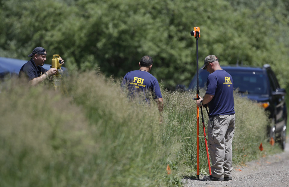Members of the FBI Evidence Response Team survey an area in Oakland Township, Mich., Monday, June 17, 2013 where officials search for the remains of Teamsters union president Jimmy Hoffa who disappeared from a Detroit-area restaurant in 1975. The search follows claims made in February by reputed Mafia captain Tony Zerilli, who told Detroit TV station WDIV that he knew where Hoffa was buried. (AP Photo/Carlos Osorio)