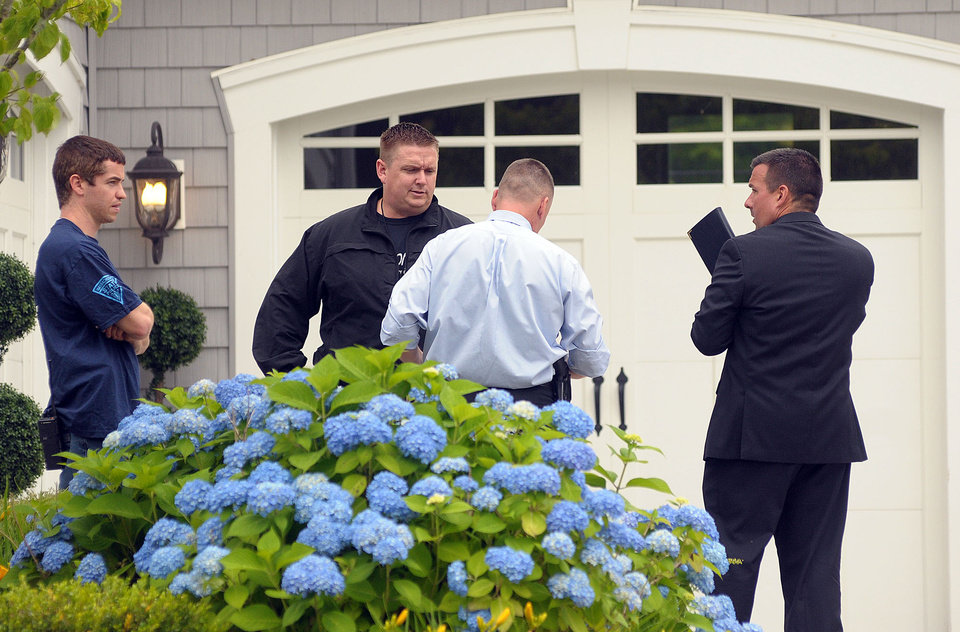 Photo - Police investigators work outside the home of former New England Patriots football player Aaron Hernandez Thursday, June 27, 2013, in North Attleboro, Mass.  A judge on Thursday denied bail for the former NFL player, who is charged with first-degree murder in the shooting death of a friend. (AP Photo/The Attleboro Sun Chronicle, Mark Stockwell)  MAGS OUT. MANDATORY CREDIT, PROVIDENCE JOURNAL OUT