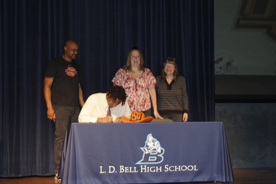 Photo - Oklahoma State football signee Jesse Robinson signs his national letters of intent at L.D. Bell High School in Hurst, Texas. PHOTO BY GINA MIZELL, The Oklahoman