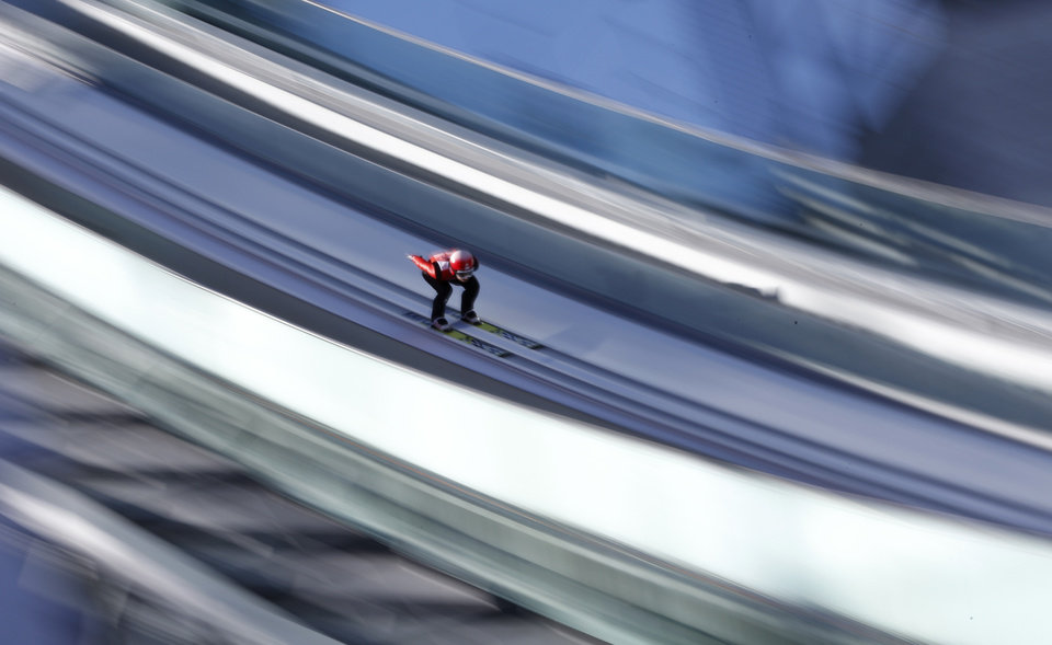 Photo - In this slow shutter speed photo Switzerland's Simon  Ammann starts an attempt during the men's normal hill ski jumping training at the 2014 Winter Olympics, Friday, Feb. 7, 2014, in Krasnaya Polyana, Russia. (AP Photo/Matthias Schrader)