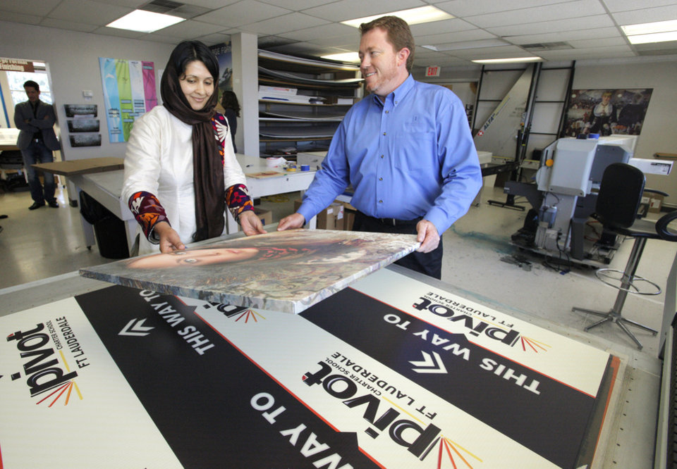Jason McWilliams, vice president of Impressions Printing, showing Freshta Hazeq, from Afghanistan, a large print done at Impressions Printing in Oklahoma City Wednesday, July 18, 2012. Freshta is in Okla. City as part of the Institute for the Economic Empowerment of Women's mentorship program. Photo by Paul B. Southerland, The Oklahoman