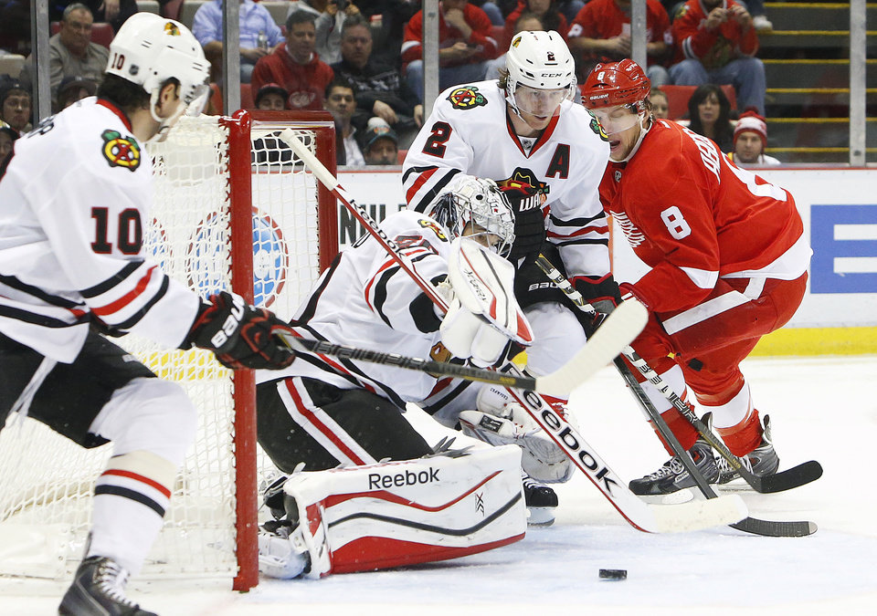 Photo - Chicago Blackhawks goalie Corey Crawford, second from left, stops a Detroit Red Wings left wing Justin Abdelkader's (8) shot in the second period of an NHL hockey game Wednesday, Jan. 22, 2014, in Detroit. (AP Photo/Paul Sancya)