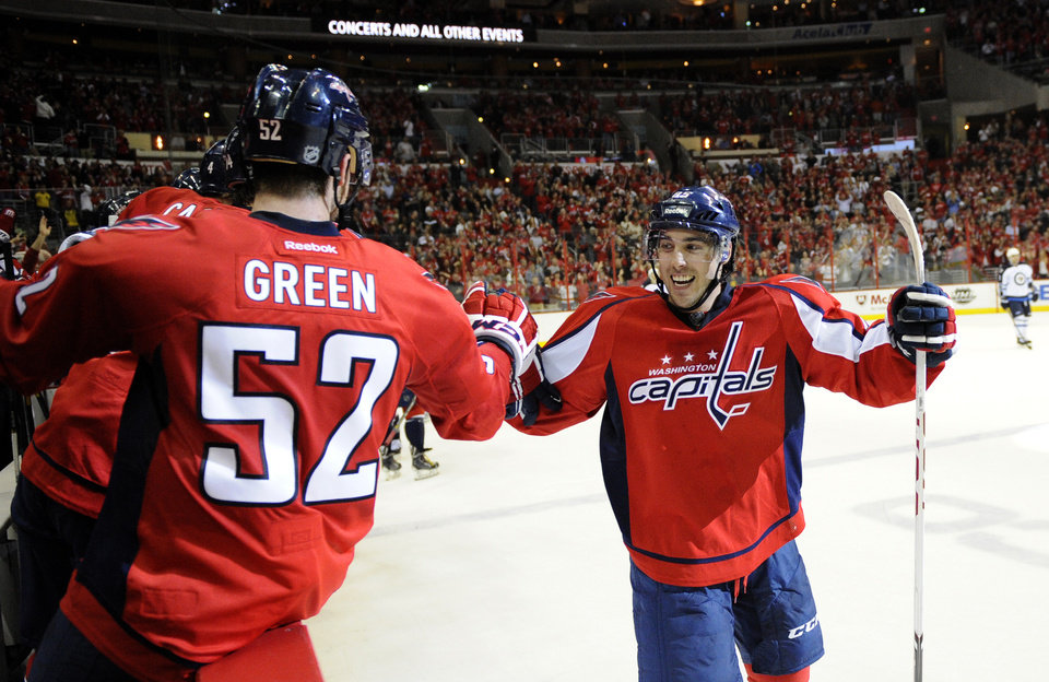 Photo - Washington Capitals center Mathieu Perreault, right, celebrates his goal with Mike Green (52) against the Winnipeg Jets during the second period of an NHL hockey game, Tuesday, April 23, 2013, in Washington. (AP Photo/Nick Wass)