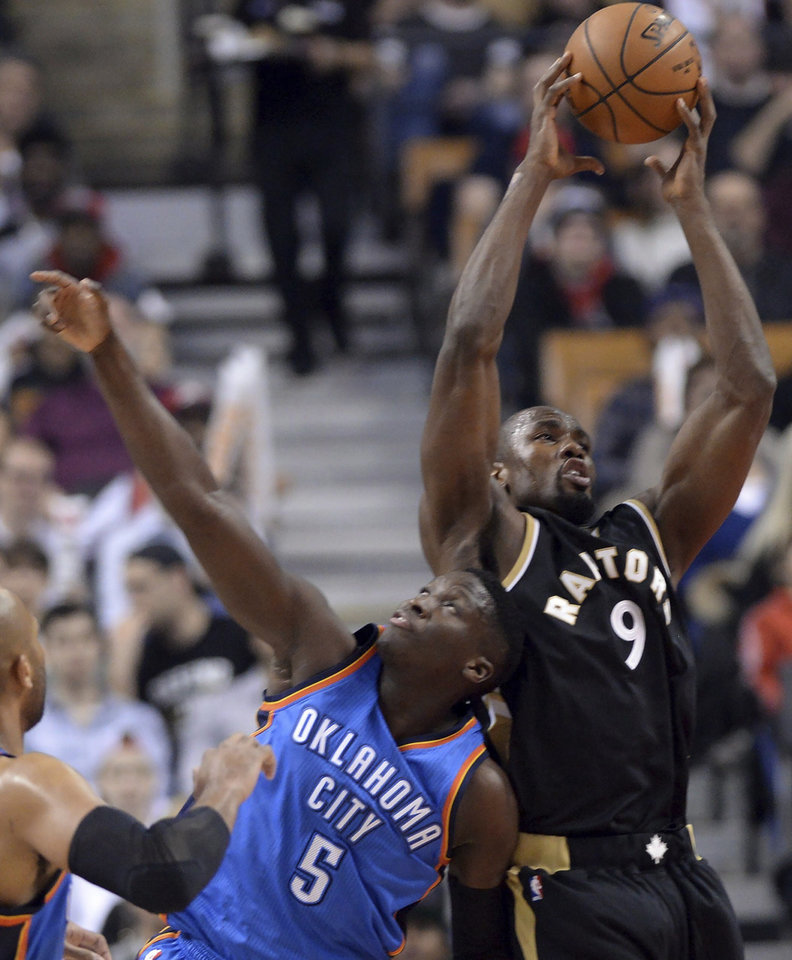 Photo - Toronto Raptors forward Serge Ibaka (9) catches the rebound next to Oklahoma City Thunder guard Victor Oladipo (5) during the first half of an NBA basketball game Thursday, March 16, 2017, in Toronto. (Nathan Denette/The Canadian Press via AP)