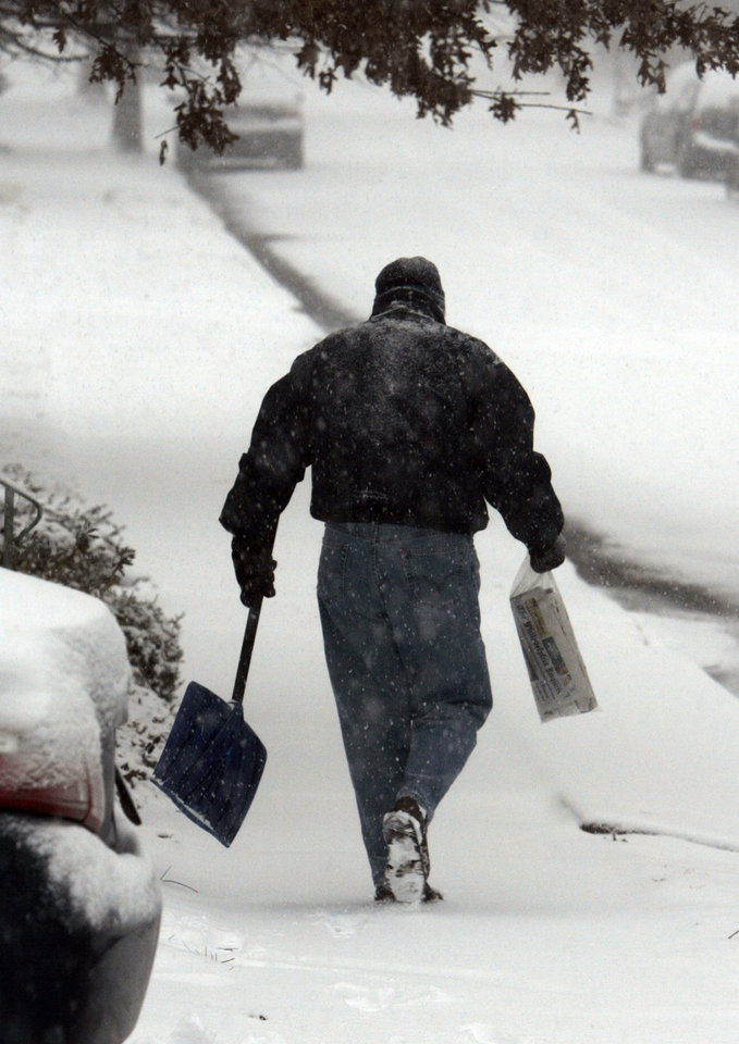 FILE - In this Dec. 19, 2009 file photo, Bill Winterle carries his neighbor's newspaper to her doorstep while shoveling his driveway during a major winter storm in Havertown, Pa. The storm hit the Mid-Atlantic and East coast areas. Securing your home and making it look occupied while you are away, and making sure packages and newspapers aren't sitting in your driveway day after day will help deter thieves. (AP Photo/Jacqueline Larma, File)