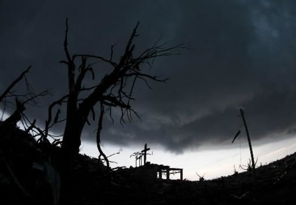 A cross stands atop a church that was severely damaged by a tornado in Joplin, Mo., as a severe storm passes overhead Monday, May 23, 2011. A large tornado moved through much of the city Sunday, damaging a hospital, hundreds of homes and businesses and killing at least 89 people. (AP Photo/Charlie Riedel)