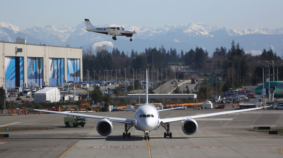 Photo - A Boeing 787 taxis as a small plane lands on Monday, March 25, 2013 at Paine Field in Everett. This was the first test flight of a 787 since the fleet was grounded because the danger of a fire with the lithium-Ion battery in the plane. (Associated Press/seattlepi.com, Joshua Trujillo)