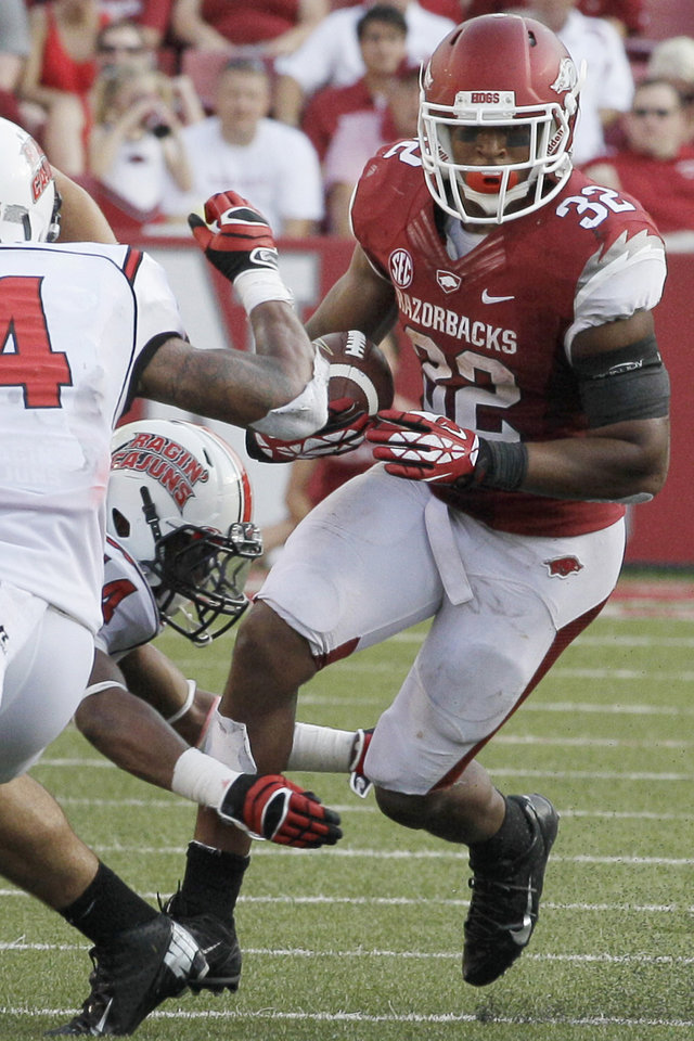 Photo - FILE - In this Aug. 31, 2013, file photo, Arkansas running back Jonathan Williams (32) carries past Louisiana-Lafayette defenders during the second half of an NCAA college football game in Fayetteville, Ark. Williams is returning to the Razorbacks in the 2014 season. (AP Photo/Danny Johnston, File)