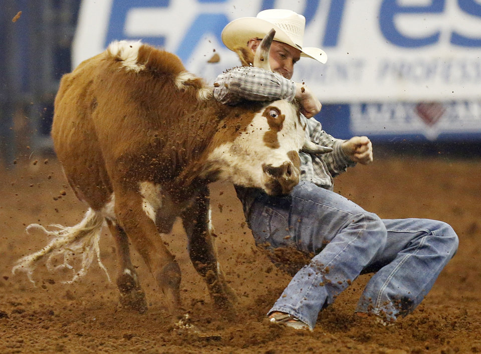 Photo - Kyle Irwin of Robertsdale, Ala., competes in steer wrestling during the National Circuit Finals Rodeo at the Lazy E Arena in Guthrie, Okla., Saturday afternoon, April 12, 2014. Photo by Nate Billings, The Oklahoman