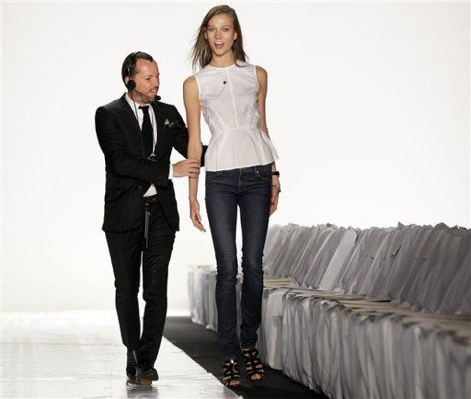 Fashion show producer Alex Betak, Director of Bureau Betak, schools model Karly Kloss on the runway before the Michael Kors Spring 2013 collection is modeled, during Fashion Week in New York,  Wednesday, Sept. 12, 2012. (AP Photo/Richard Drew)