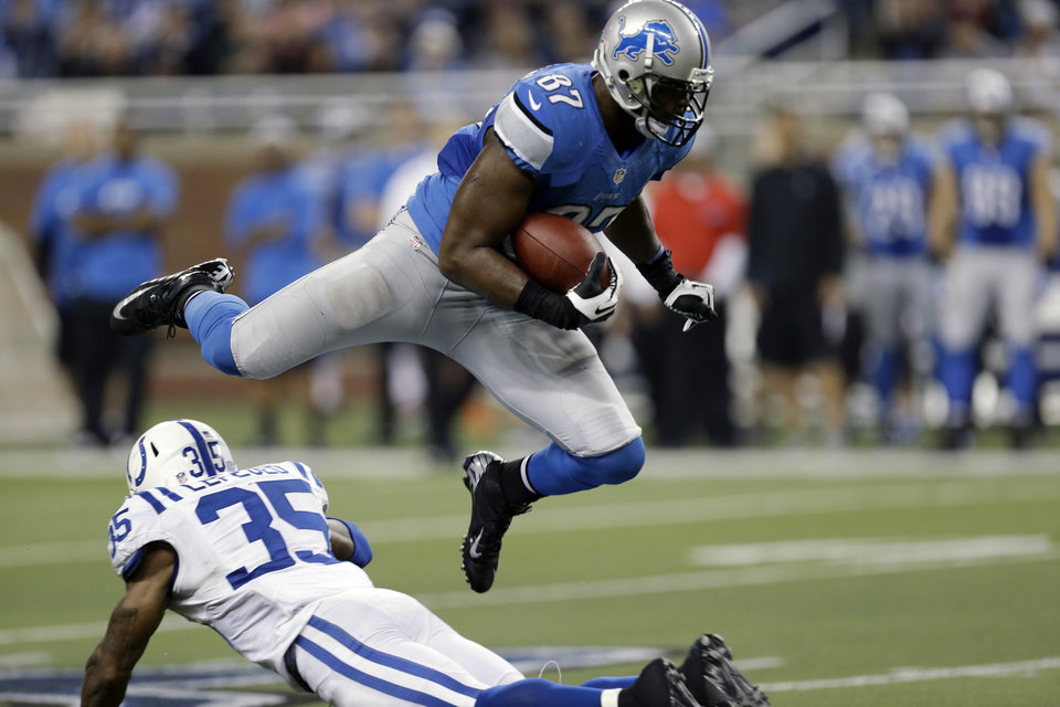 Photo - Detroit Lions tight end Brandon Pettigrew (87) leaps over Indianapolis Colts strong safety Joe Lefeged (35) during the second quarter of an NFL football game at Ford Field in Detroit, Sunday, Dec. 2, 2012. (AP Photo/Paul Sancya)