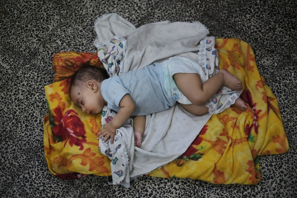 Photo - Three-month-old Palestinian baby girl Mayar Al Masri sleeps in a classroom at a United Nations school where hundreds of families have sought refuge after fleeing their homes following heavy Israeli forces' strikes, in Jebaliya refugee camp, Gaza Strip, Friday, July 25, 2014. Over 140,000 Palestinians are seeking shelter in 83 UNRWA schools, according to UNRWA spokesman Chris Gunness. The number of Palestinians seeking shelter since the ground operation began has increased seven-fold. (AP Photo/Lefteris Pitarakis)