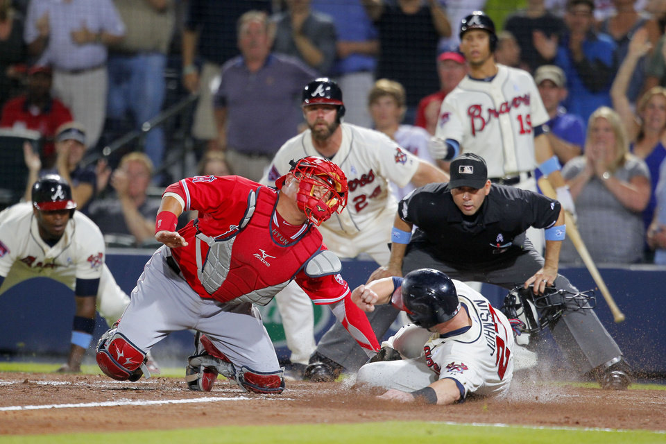 Photo - Los Angeles Angels catcher Hank Conger (16) tags out Atlanta Braves Chris Johnson (23) at the plate after Tommy La Stella brings in two runs in the sixth inning of an interleague baseball game Sunday, June 15, 2014, in Atlanta. (AP Photo/Todd Kirkland)