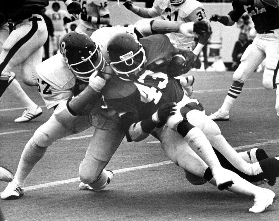 University of Oklahoma nose guard Reggie Kinlaw (62) wrestles down Oklahoma State University running back Terry Miller (43) during Bedlam college football game action in Stillwater, Okla, Nov. 5, 1977.  The Sooners downed the Cowboys, 61-28. Staff photo