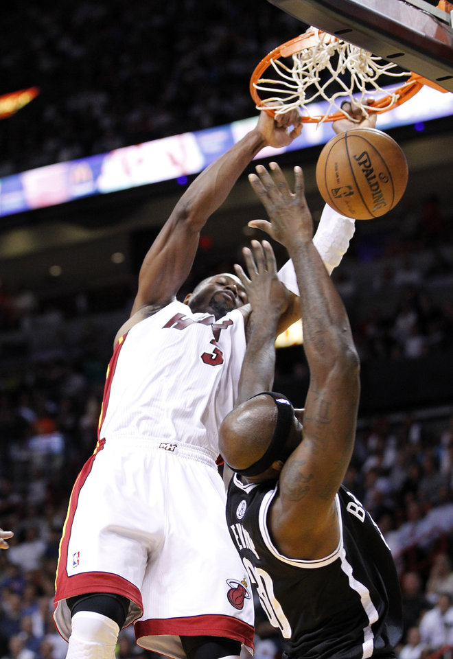 Miami Heat guard Dwyane Wade dunks the ball against Brooklyn Nets forward Reggie Evans, right, during the first half of an NBA basketball game, Wednesday, Nov. 7, 2012, in Miami. (AP Photo/Wilfredo Lee)