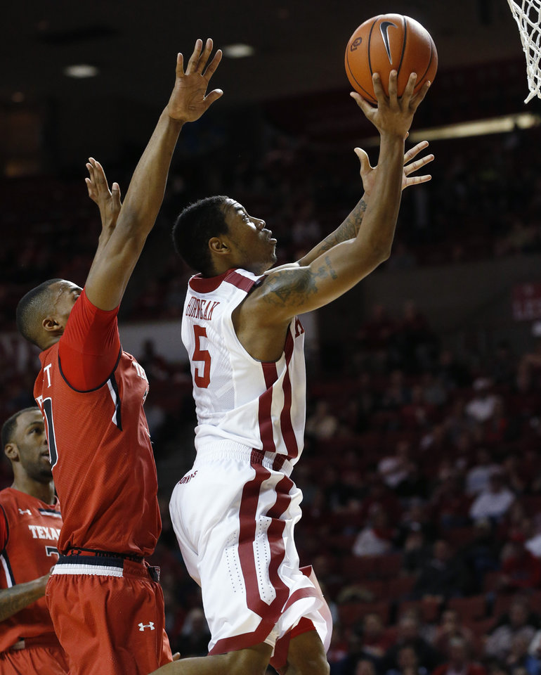 Photo - Oklahoma guard Je'lon Hornbeak (5) shoots in front of Texas Tech forward Jaye Crockett (30) during the second half of an NCAA college basketball game in Norman, Okla., Wednesday, Feb. 12, 2014. Texas Tech won 68-60. (AP Photo/Sue Ogrocki)