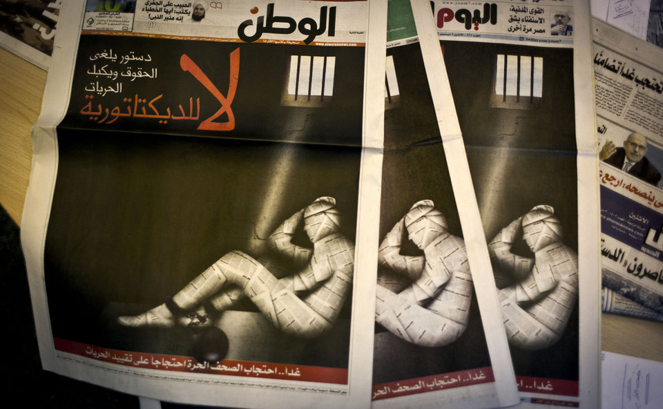 "Copies of Egypt's most prominent newspapers running black background front pages with Arabic that reads, ""no to dictatorship, tomorrow free newspapers will obscure to protest the freedom's restrictions"" and a picture of a man wrapped in newspaper with his feet cuffed, at the editorial room of Al Masry Al Youm daily newspaper in Cairo, Egypt, Monday, Dec. 3, 2012. Eleven Egyptian newspapers are planning to suspend publication on Tuesday to protest against President Mohammed Morsi's decision to call a constitution referendum on 15 December. (AP Photo/Nasser Nasser)"