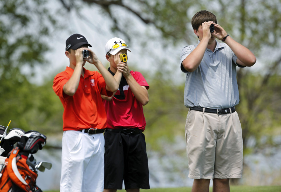 From left, Nick Pierce of Sallisaw, Cody Shore of Poteau and Quade Cummins of Weatherford look through rangefinder devices before hitting off the 18th tee box during Class 4A boy's state golf  tournament on Tuesday, May 7, 2013,  at  Hefner Golf Course in Oklahoma City.   Photo  by Jim Beckel, The Oklahoman.