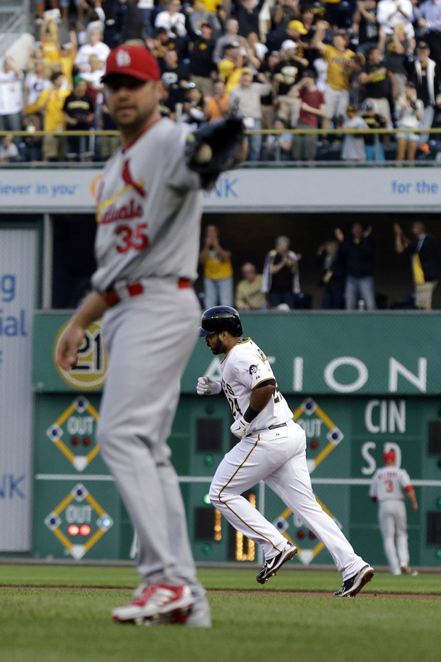 Photo - Pittsburgh Pirates' Pedro Alvarez, right, rounds the bases after hitting a three-run home run off St. Louis Cardinals starting pitcher Jake Westbrook (35) during the first inning of a baseball game in  Pittsburgh Monday, July 29, 2013. (AP Photo/Gene J. Puskar)