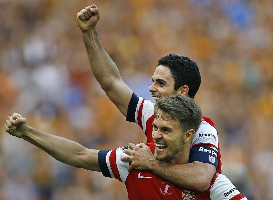 Photo - Arsenal's Aaron Ramsey, front, celebrates with Mikel Arteta after his team won the English FA Cup final soccer match between Arsenal and Hull City at Wembley Stadium in London, Saturday, May 17, 2014. Arsenal won 3-2 after extra-time. (AP Photo/Kirsty Wigglesworth)