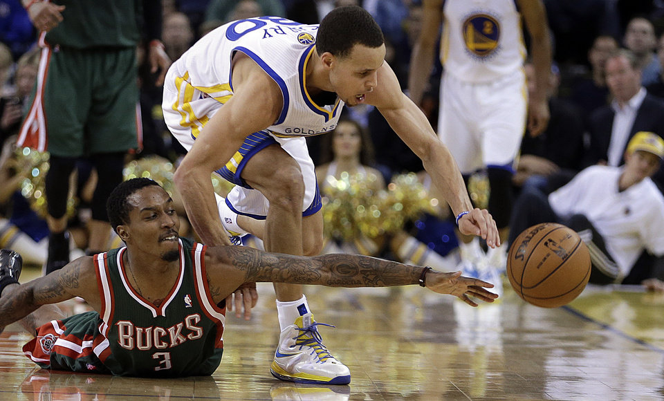 Milwaukee Bucks' Brandon Jennings (3) and Golden State Warriors' Stephen Curry chase a loose ball during the second half of an NBA basketball game Saturday, March 9, 2013, in Oakland, Calif. (AP Photo/Ben Margot)