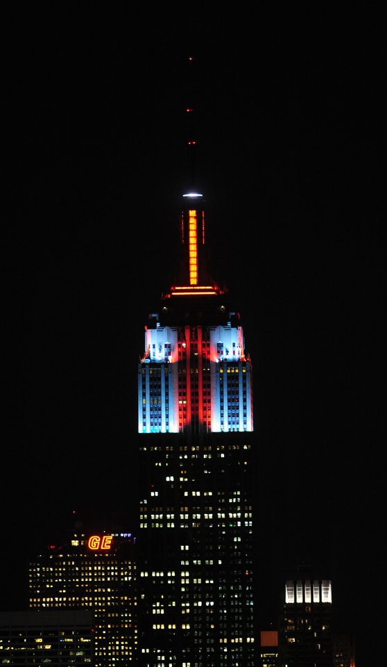 In this Nov. 26, 2012, photo provided by the Empire State Building, the top floors of New York\'s Empire State Building are lit in gold, red, blue and white light after they being switched on by R&B star Alicia Keys. The landmark boasts a new LED lighting system with a palette of more than 16 million colors in limitless combinations, including ripples, sparkles, chasers, sweeps, strobes and bursts. The old lights came in only 10 colors. (AP Photo/Empire State Building, Bryan Smith)