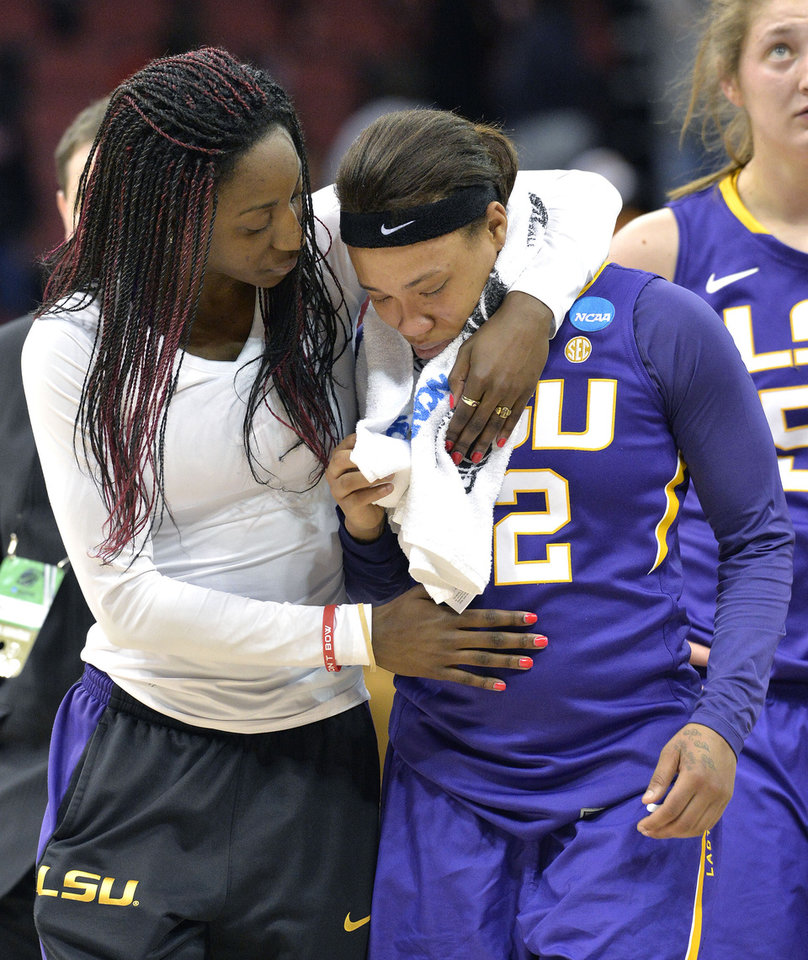 Photo - LSU assistant coach Tasha Butts embraces Danielle Ballard following their loss to Louisville in a regional semifinal game at the NCAA women's college basketball tournament on Sunday, March 30, 2014, in Louisville, Ky. Louisville defeated LSU 73-47. (AP Photo/Timothy D. Easley)