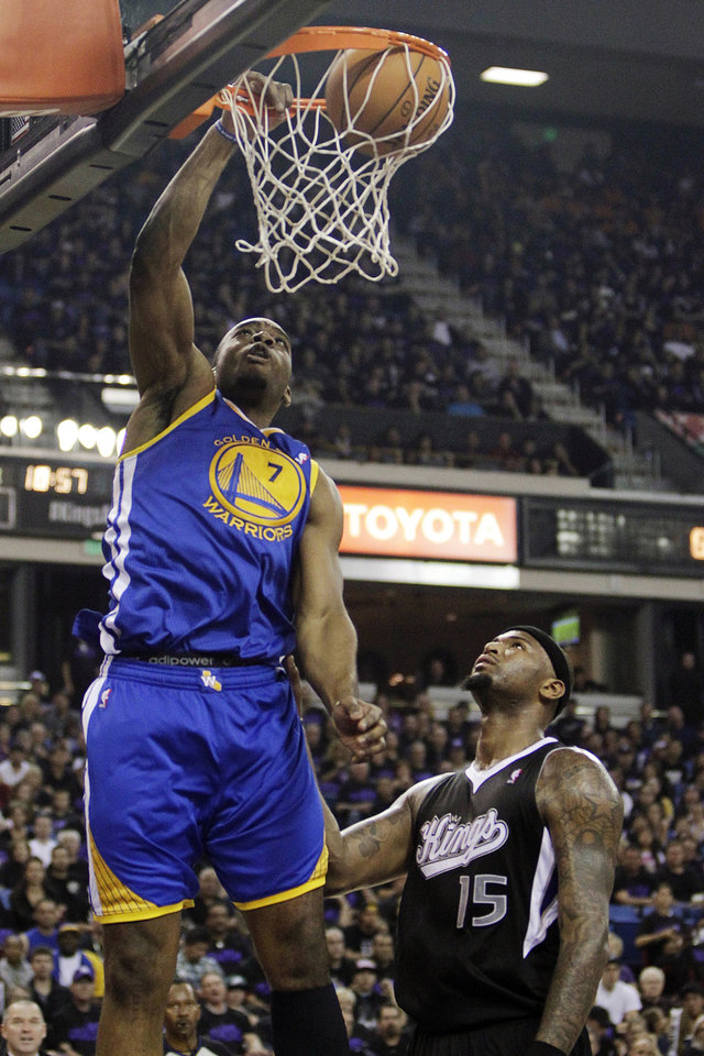 Photo -   Golden State Warriors forward Carl Landry, left, dunks over Sacramento Kings center DeMarcus Cousins during the first half of an NBA basketball game in Sacramento, Calif., Monday, Nov. 5, 2012. (AP Photo/Rich Pedroncelli)