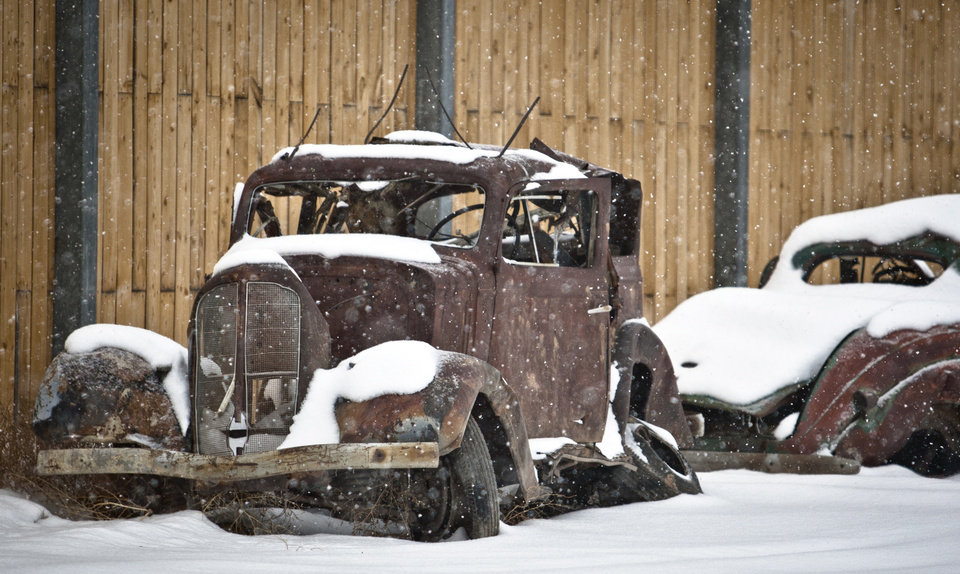 Photo - The rusted frame of a classic car sits along a fence row near West Blackfoot Street in the south part of Laramie, Wyo., during a springtime snowfall, Tuesday, April 9, 2013. (AP Photo/Laramie Boomerang, Jeremy Martin)