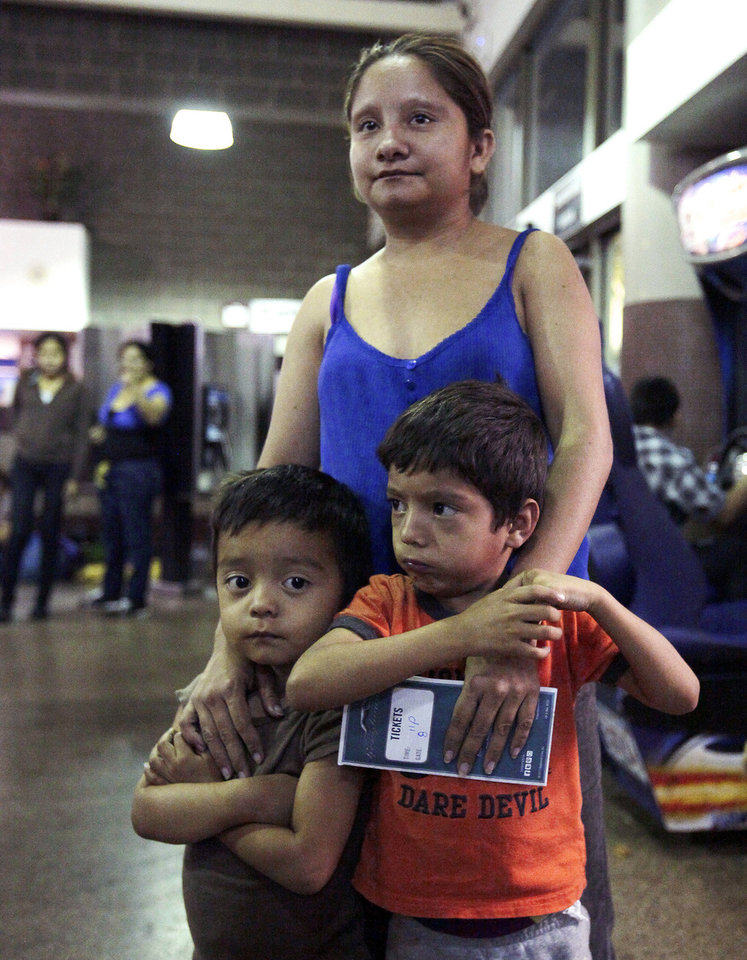 Photo - Floridalma Bineda Portillo, of Guatemala, and her sons, wait at the at the Greyhound bus terminal, Thursday, May 29, 2014 in Phoenix. About 400 mostly Central American women and children caught crossing from Mexico into south Texas were flown to Arizona this weekend after border agents there ran out of space and resources.  Officials then dropped hundreds of them off at Phoenix and Tucson Greyhound stations, overwhelming the stations and humanitarian groups who were trying to help. (AP Photo/Rick Scuteri)