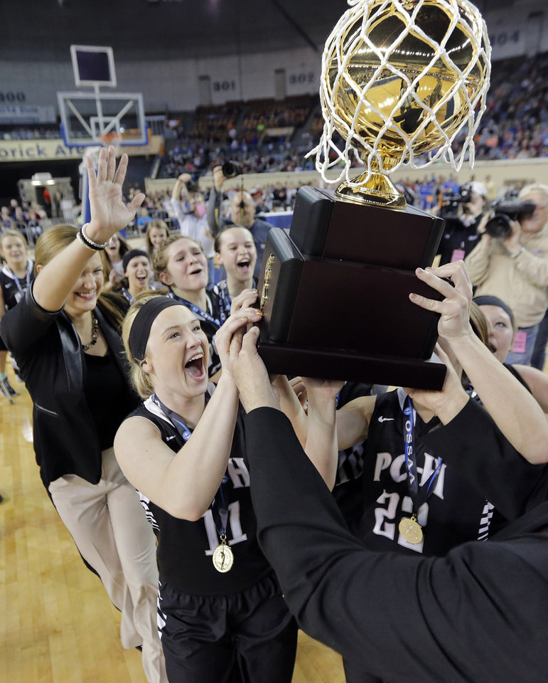 Photo - Pond Creek-Hunter celebrates with the gold ball trophy after winning the Class A girls high school basketball state championship game between Seiling and Pond Creek-Hunter at the State Fair Arena in Oklahoma City, Okla., on Saturday, March 8, 2014.  Photo by Chris Landsberger, The Oklahoman