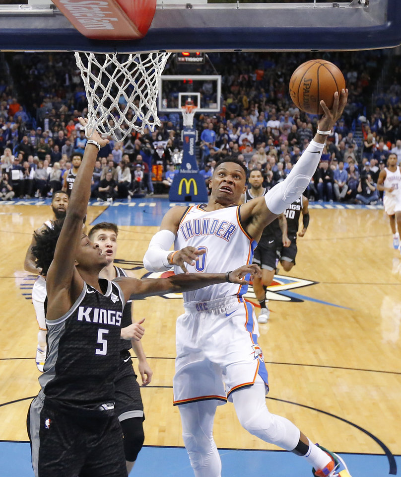 Photo - Oklahoma City's Russell Westbrook (0) goes to the basket beside Sacramento's De'Aaron Fox (5) during an NBA basketball game between the Oklahoma City Thunder and the Sacramento Kings at Chesapeake Energy Arena in Oklahoma City, Saturday, Feb. 23, 2019. Sacramento won 119-116. Photo by Bryan Terry, The Oklahoman