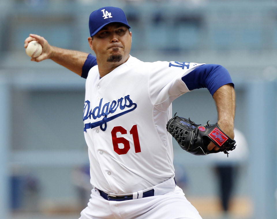 Photo - Los Angeles Dodgers starting pitcher Josh Beckett (61) throws against the Chicago Cubs in the first inning of a baseball game on Sunday, Aug. 3, 2014, in Los Angeles. (AP Photo/Alex Gallardo)