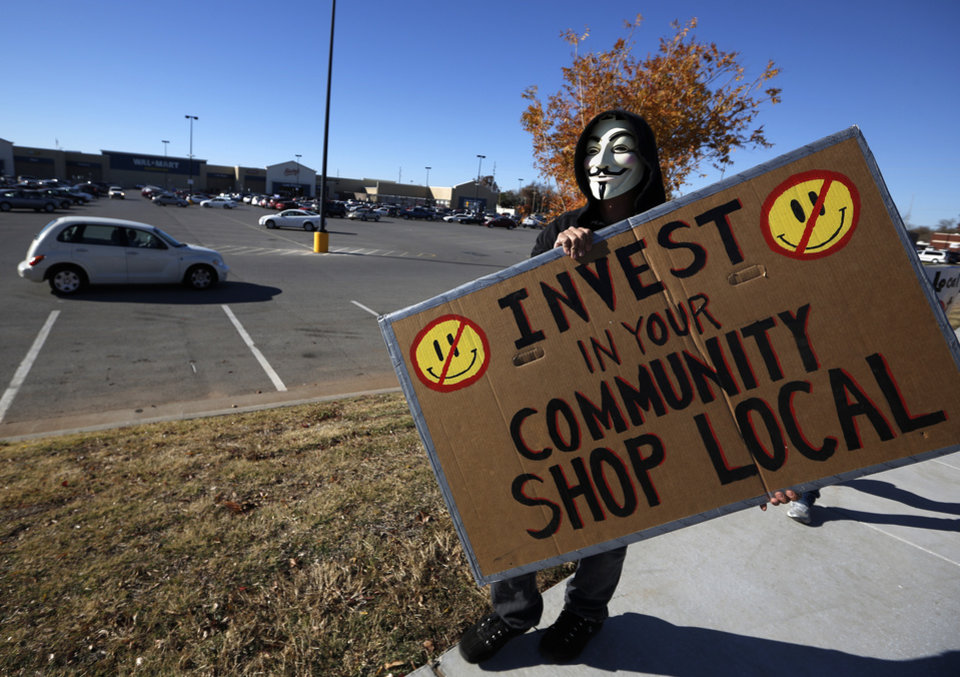 Rob Shawnee walks with a sign during an Occupy OKC demonstration at a Wal-Mart in Del City, Friday, Nov. 23, 2012.  Members of the Occupy movement were protesting for Wal-Mart worker's rights to a living wage.  Photo by Garett Fisbeck, The Oklahoman