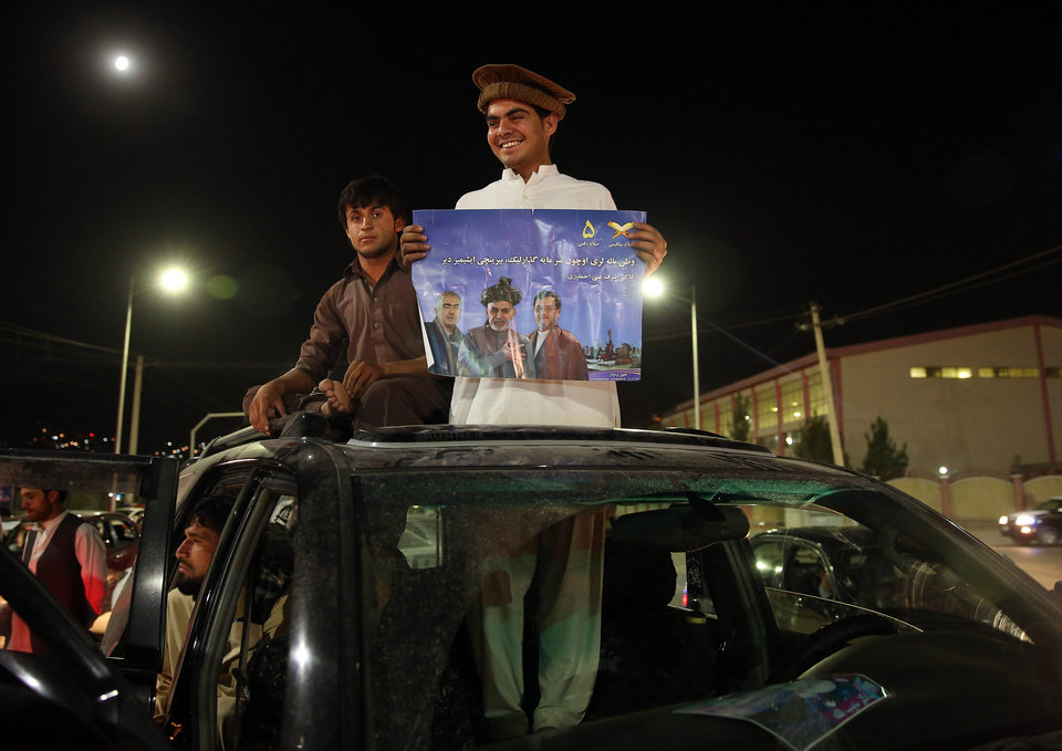 Photo - A supporter of Afghanistan's presidential candidate Ashraf Ghani Ahmadzai, holds his poster as he and scores of others celebrate in Kabul, Afghanistan, Monday, July 7, 2014.  Afghan officials released preliminary election results Monday showing former finance minister Ashraf Ghani Ahmadzai well in the lead for the presidency but said no winner can be declared because millions of ballots were being audited for fraud. The announcement came as Ahmadzai is locked in a standoff with his rival Abdullah Abdullah, who has refused to accept any results until all fraudulent ballots are invalidated. (AP Photo/Massoud Hossaini)